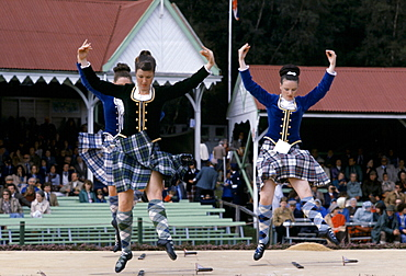 Scottish girls in tartan kilts dancing the sword dance at the Braemar Royal Highland Gathering, the Braemar Games in Scotland