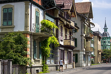 Jogger passes traditional houses in Neugasse at Interlaken in the Bernese Oberland, Switzerland, Europe