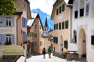 Tourists pass Hotel Meisser in Engadine Valley village of Guarda, renowned for its painted stone 17th century buildings, Graubunden, Switzerland, Europe