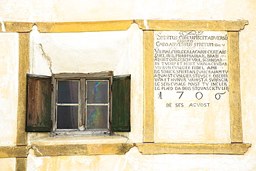 Window and inscription on old painted stone 17th century building in the Engadine Valley in the village of Guarda, Graubunden, Switzerland, Europe