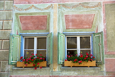 Windows in old painted stone 17th century building in the Engadine Valley in the village of Guarda, Graubunden, Switzerland, Europe