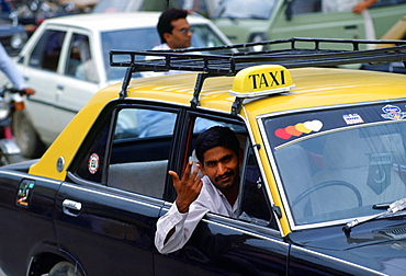 Taxi driver in Islamabad, Pakistan gesturing with his hand as he leans out of his car window.