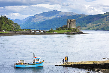 Fishermen fishing by Eilean Donan Castle, a Highland fortress, with Saltire Scottish flag flying in Loch Alsh at Dornie, Kyle of Lochalsh in the western hIghlands of Scotland, United Kingdom, Europe