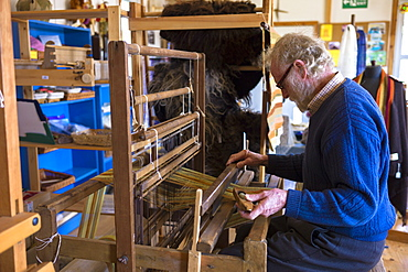 Craftsman using traditional loom to weave wool into handmade scarf at Croft Wools and Weavers, Applecross in the Highlands of Scotland, United Kingdom, Europe