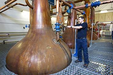 Stillsman inspecting copper spirit stills in the Stillshouse at Talisker Whisky Distillery making single malt whisky in Carbost on Isle of Skye, Scotland, United Kingodm, Europe