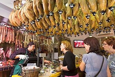 Shoppers in butcher's shop to buy Iberico Jamon Ham and other meats in Calle de Bidebarrieta in Bilbao, Euskadi, Spain, Europe