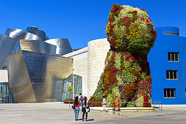 Tourists view Puppy flower feature floral art by Jeff Koons at Guggenheim Museum in Bilbao, Basque Country, Euskadi, Spain, Europe