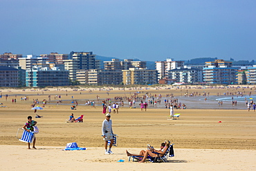 Beach scene and people sunbathing on summer holiday in Laredo, Cantabria, Spain, Europe