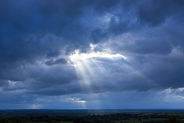 Rays of the sun break through cloudy stormy sky in inclement weather, England, United Kingdom, Europe