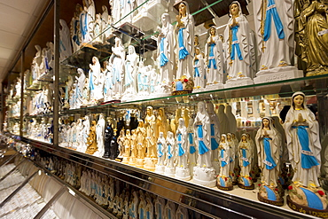 Religious icons and statues of Our Lady and St. Bernadette on shelves in shop at pilgrimage location of Lourdes, Pyrenees, France, Europe