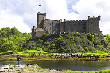 Tourist taking photographs at Highland fortress Dunvegan Castle, the ancestral home of the MacLeod clan, and loch on the Isle of Skye, Inner Hebrides, Scotland, United Kingdom, Europe