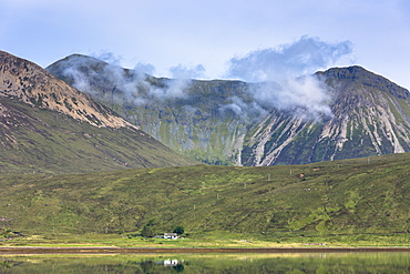Small white solitary crofters cottage nestling below mountain range reflected in waters of the loch, Isle of Skye, Inner Hebrides, Highlands and Islands, Scotland, United Kingdom, Europe