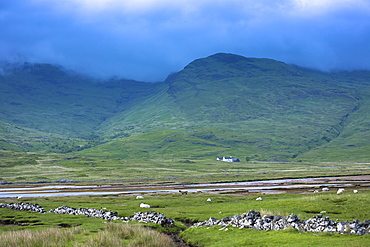 Small white solitary crofters cottage nestling below mountain range by loch on Isle of Mull, Inner Hebrides and Western Isles, Scotland, United Kingdom, Europe