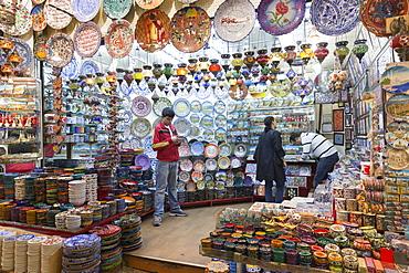 Man using smartphone in ceramics and souvenirs stall in The Grand Bazaar (Great Bazaar) (Kapali Carsi), Beyazi, Istanbul, Turkey, Europe