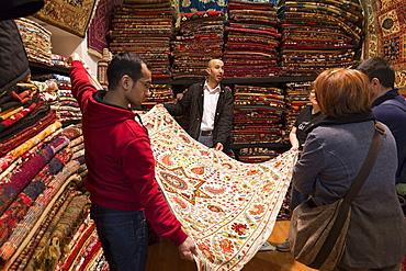 Salesman with traditional Turkish carpet in The Grand Bazaar (Great Bazaar) (Kapali Carsi), Beyazi, Istanbul, Turkey, Europe