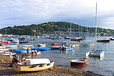 Boats in the harbour and family group on beach at coastal resort of Teignmouth in South Devon, England, United Kingdom, Europe