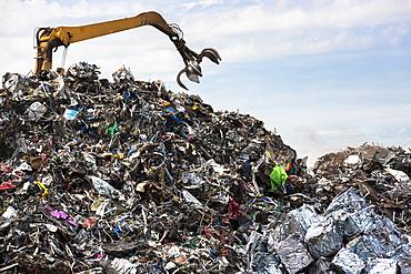 Grab machine organising metal recycling of scrap metal to avoid environmental pollution in England, United Kingdom, Europe