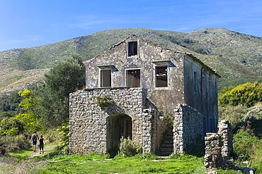 Tourists visiting Skordilis Mansion house ruin in oldest village of Corfu, ancient Old Perithia (Palea Perithea), Corfu, Greek Islands, Greece, Europe