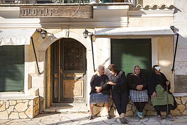 Elderly Corfiot women wearing traditional black clothes sitting relaxing in village square of Krini, Corfu, Greek Islands, Greece, Europe