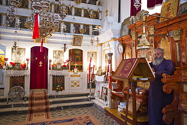 Greek Orthodox priest reading Bible inside chapel of Christian church at Krini, Corfu, Greek Islands, Greece, Europe