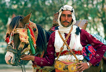 A horseman in traditional dress holding his horse which has eye defenders against the sun and dust.