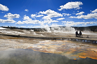 Cold tourists on seat surrounded by steam, Upper Geyser Basin, Yellowstone National Park, UNESCO World Heritage Site, Wyoming, United States of America, North America