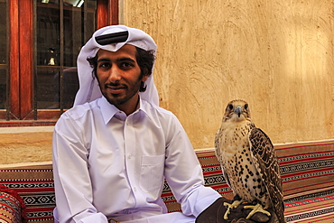 Seated man in traditional dress relaxes with his falcon at the Falcon Souq, Doha, Qatar, Middle East