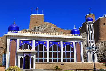 Blue domed mosque with minaret and Al-Mirani Fort, Old Muscat, Oman, Middle East