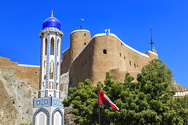 Blue domed mosque minaret, Oman, Middle Easti National Flag and Al-Mirani Fort, Old Muscat, Oman, Middle East