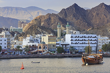Mutrah Corniche and entrance to Mutrah Souq, backed by mountains, viewed from the sea, Muscat, Oman, Middle East