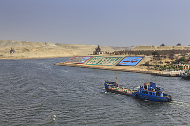Small ship travels on the Suez Canal, past memorials and a large Welcome to Egypt sign, Ismalia, Egypt, North Africa