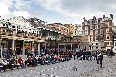 Juggler performs to a large crowd, Piazza and Central Market, Covent Garden, London, England, United Kingdom, Europe
