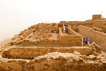 Tourists at Masada fortress ruins, air thick with desert sand, UNESCO World Heritage Site, Israel, Middle East