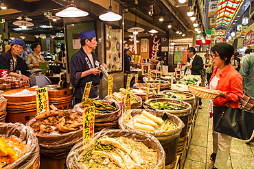 Shopper with basket considers purchase at local Japanese food stall, Nishiki Market (Kyoto's Kitchen), Downtown Kyoto, Japan, Asia