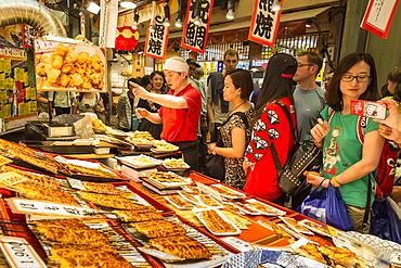 Customers queue at busy local Japanese teriyaki food stall, Nishiki Market (Kyoto's Kitchen), Downtown Kyoto, Japan, Asia