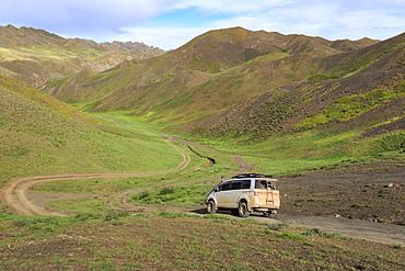 Vehicle travels off road through lush mountains, Gurvan Saikhan National Park, near Yolyn Am (Yol Valley), Gobi Desert, Mongolia, Central Asia, Asia