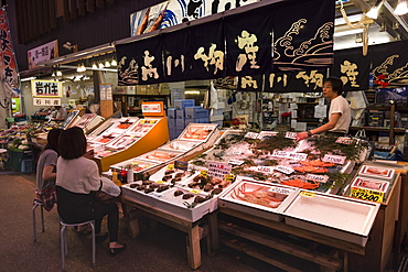Diners sit and talk to seafood stall owner, Omicho fresh food market, network of covered stall lined streets, Kanazawa, Japan, Asia