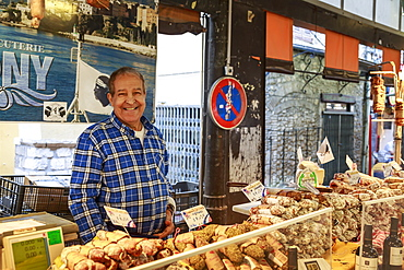 Smiling charcuterie stall holder, Marche Provencal, morning market, Vieil Antibes, French Riviera, Cote d'Azur, Provence, France, Europe