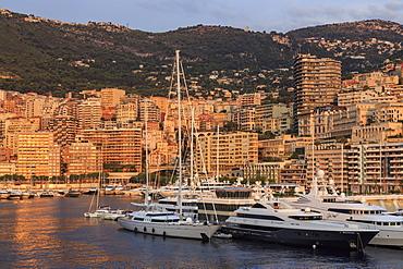Yachts in the glamorous Port of Monaco (Port Hercules) at sunrise, from the sea, Monte Carlo, Monaco, Mediterranean, Europe