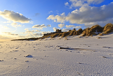 Fresh Spring snow at dawn highlight ripples and marks in the sand beneath Bamburgh Castle,  Bamburgh, Northumberland, England