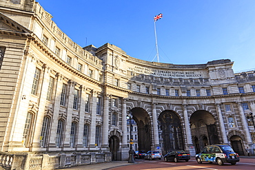 Admiralty Arch with traffic leaving The Mall and Union Flag flying, late autumn sun, London, England, United Kingdom, Europe