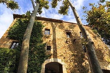 Gala Dali Castle Museum facade amidst tall trees, medieval home of Salvador Dali, Pubol, Baix Emporda, Girona, Catalonia, Spain, Europe