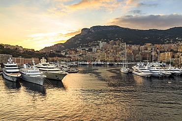 Vivid sunset over super yachts, glamorous harbour of Monaco (Port Hercules), from the sea, Monte Carlo, Monaco, Cote d'Azur, Mediterranean, Europe