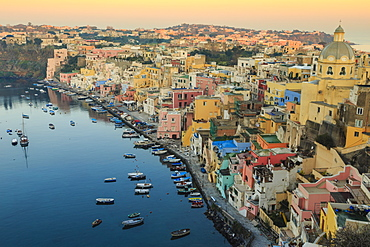 Marina Corricella at sunrise, fishing village, colourful houses, church and harbour boats, Procida Island, Bay of Naples, Campania, Italy, Europe