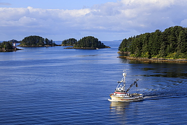 Commercial fishing boat and small forested islands, rare summer sun, Sitka Sound, Sitka, Baranof Island, Southeast Alaska, United States of America, North America