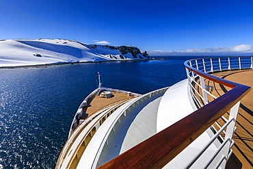 Cruise ship deck with couple in hot tub, off Half Moon Island, blue sky and evening sun, South Shetland Islands, Antarctica, Polar Regions