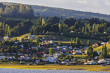 Village on shores of Castro inlet, lush rolling green hills and trees, Isla Grande de Chiloe, Chilean Lake District, Chile, South America