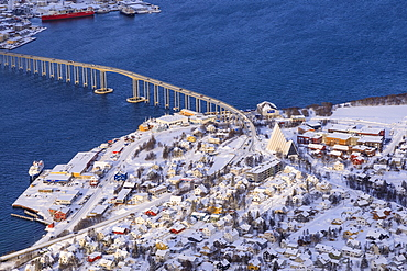 Sunlit Tromsdalen, Arctic Cathedral and Tromso Bridge, fresh snow, elevated view from Mount Storsteinen in winter, Troms, Norway, Scandinavia, Europe