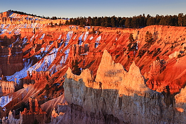 Hoodoos, rim and snow lit by strong dawn light, Queen's Garden Trail at Sunrise Point, Bryce Canyon National Park, Utah, United States of America, North America