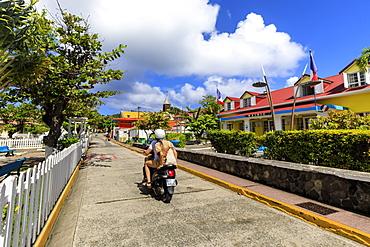 Couple on moped, colourful Bourg des Saintes town, Terre de Haut, Iles Des Saintes, Les Saintes, Guadeloupe, Leeward Islands, West Indies, Caribbean, Central America